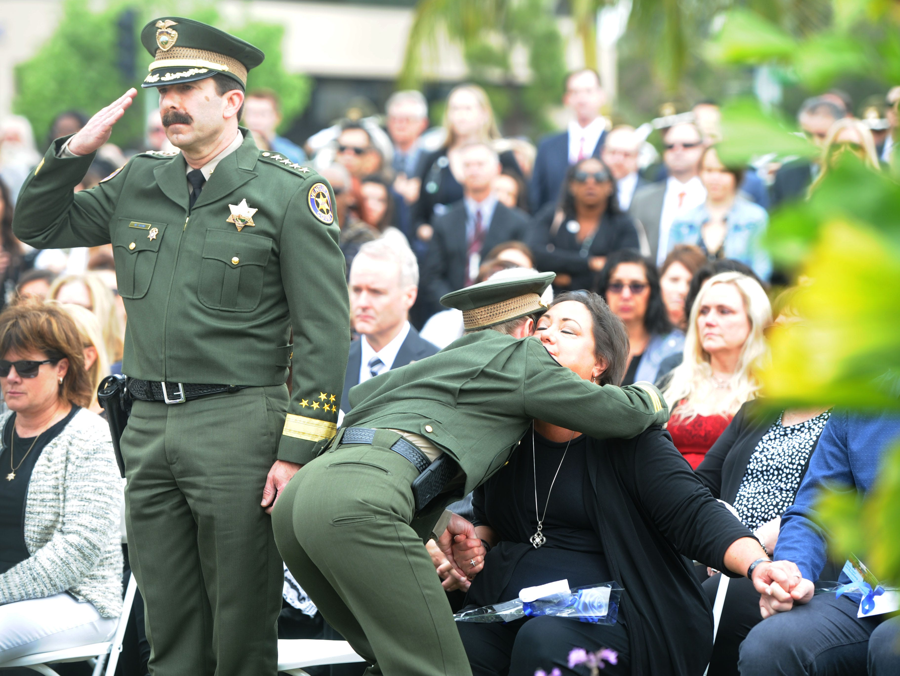 Ventura County Sheriff Bill Ayub, left, salutes as Undersheriff Monica McGrath hugs Karen Helus at the Ventura County Peace Officers Memorial. The late Sgt. Ron Helus was among those honored in a ceremony Thursday at the Ventura County Government Center.