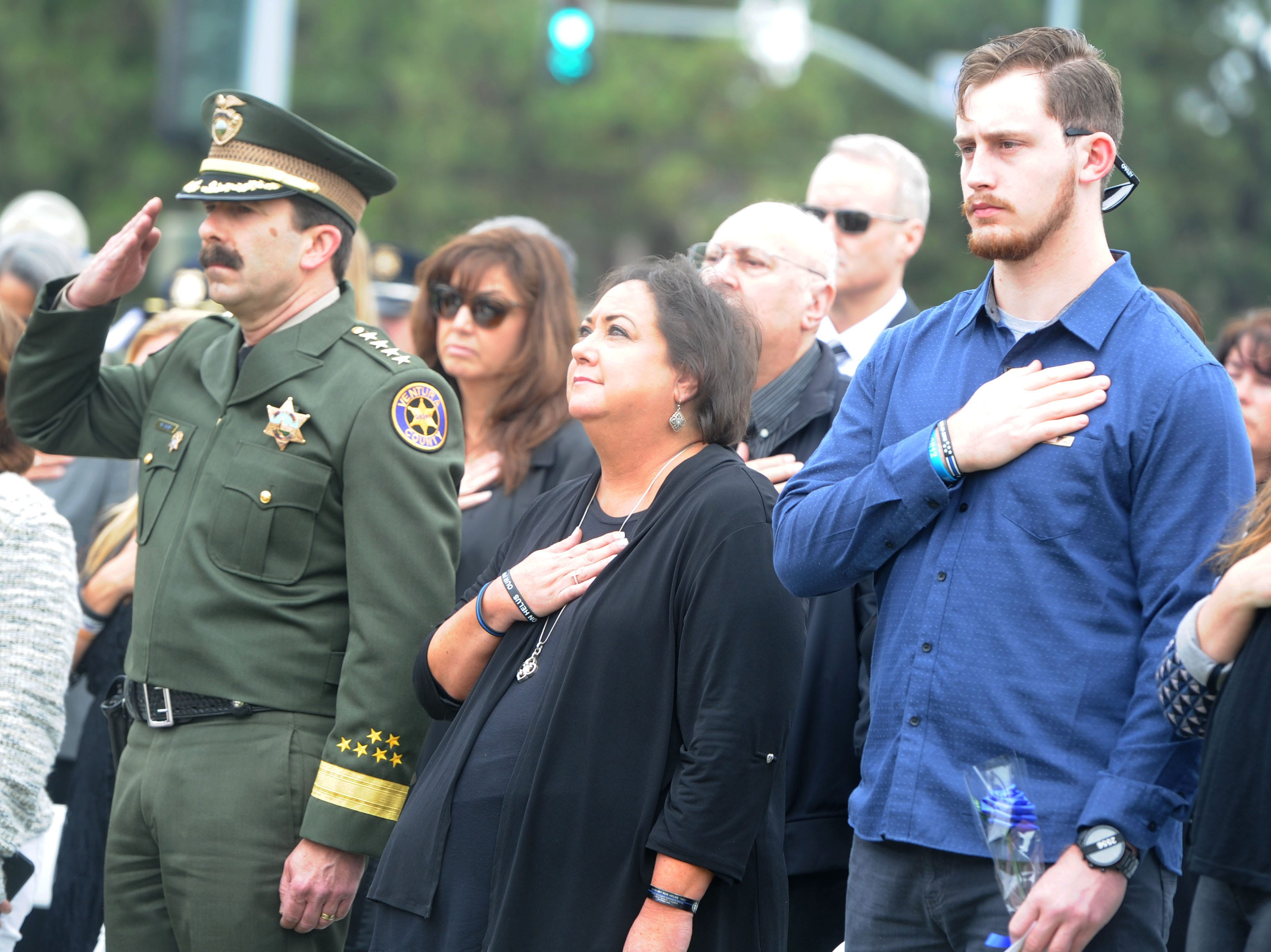 From left, Sheriff Bill Ayub, Karen Helus and Jordan Helus stand as the names of fallen officers are read Thursday at the Ventura County Peace Officers Memorial.