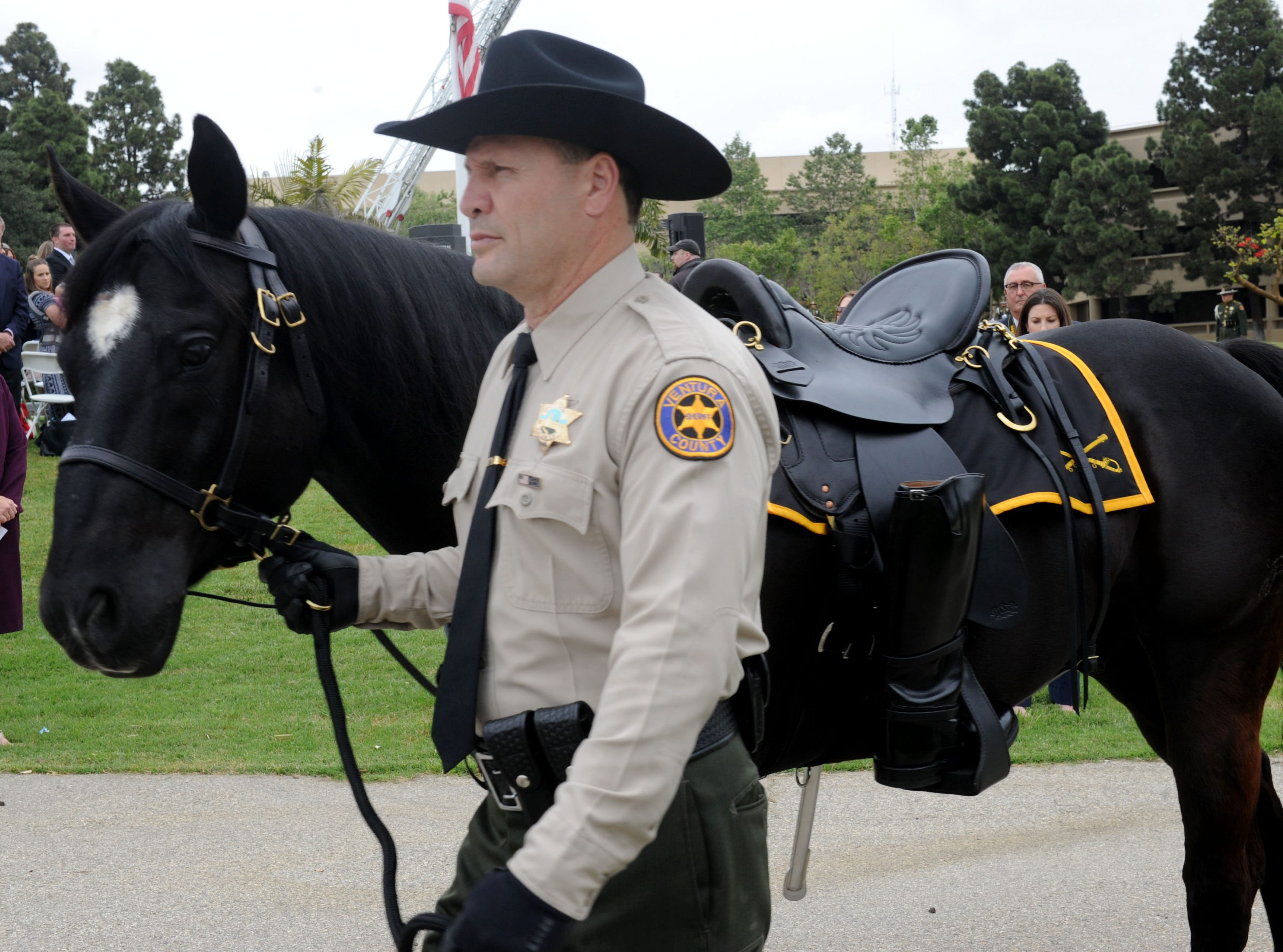 Deputy James Evans walks Tahoe as the riderless horse at the Ventura County Peace Officers Memorial on Thursday. A ceremony at the Ventura County Government Center honored the late Sgt. Ron Helus and other fallen law enforcement officers.