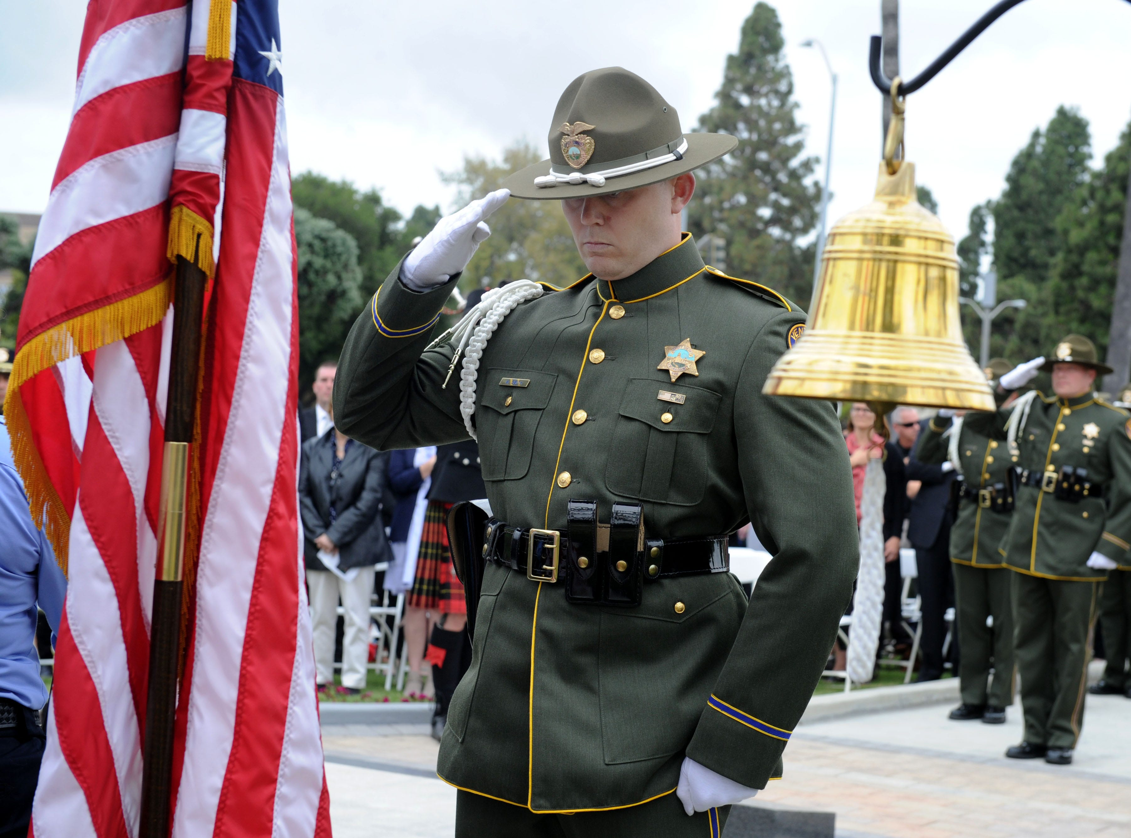 Matt Smith, with the honor guard, salutes the flag at the Ventura County Peace Officers Memorial on Thursday in Ventura.