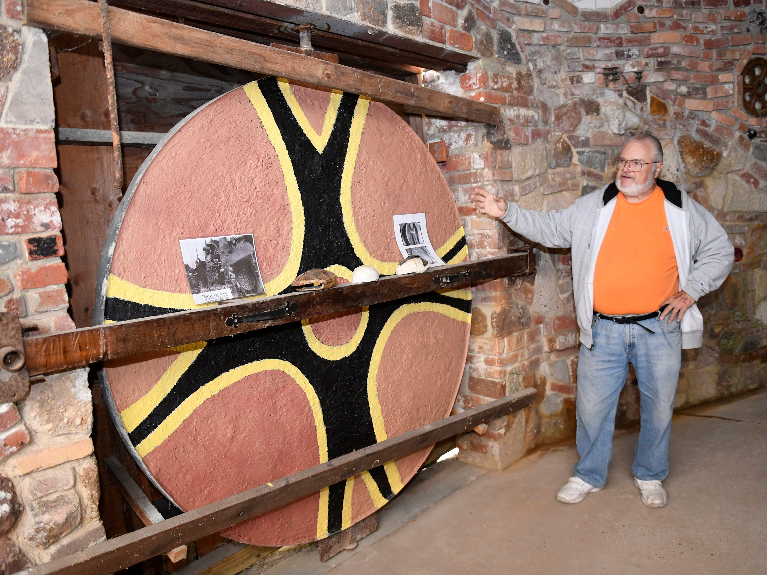 """Kevin J. Kirchner, president of the Palace of Depression Restoration Association, stands in front of the """"Turtle Shell Door"""" on Thursday, May 9, 2019."""