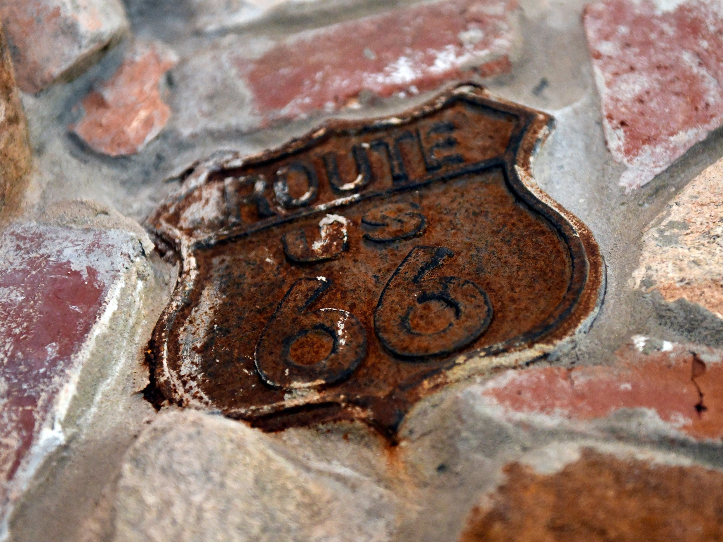 Various metal trinkets, cast concrete figures and colored glass bottles are embedded throughout the brick walls of the Palace of Depression including this Route 66 sign.