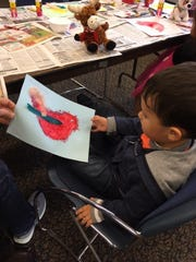 Silas Padgett, 2, shows off a painting he created during a Wee Read program at the Cumberland County Library in Bridgeton.