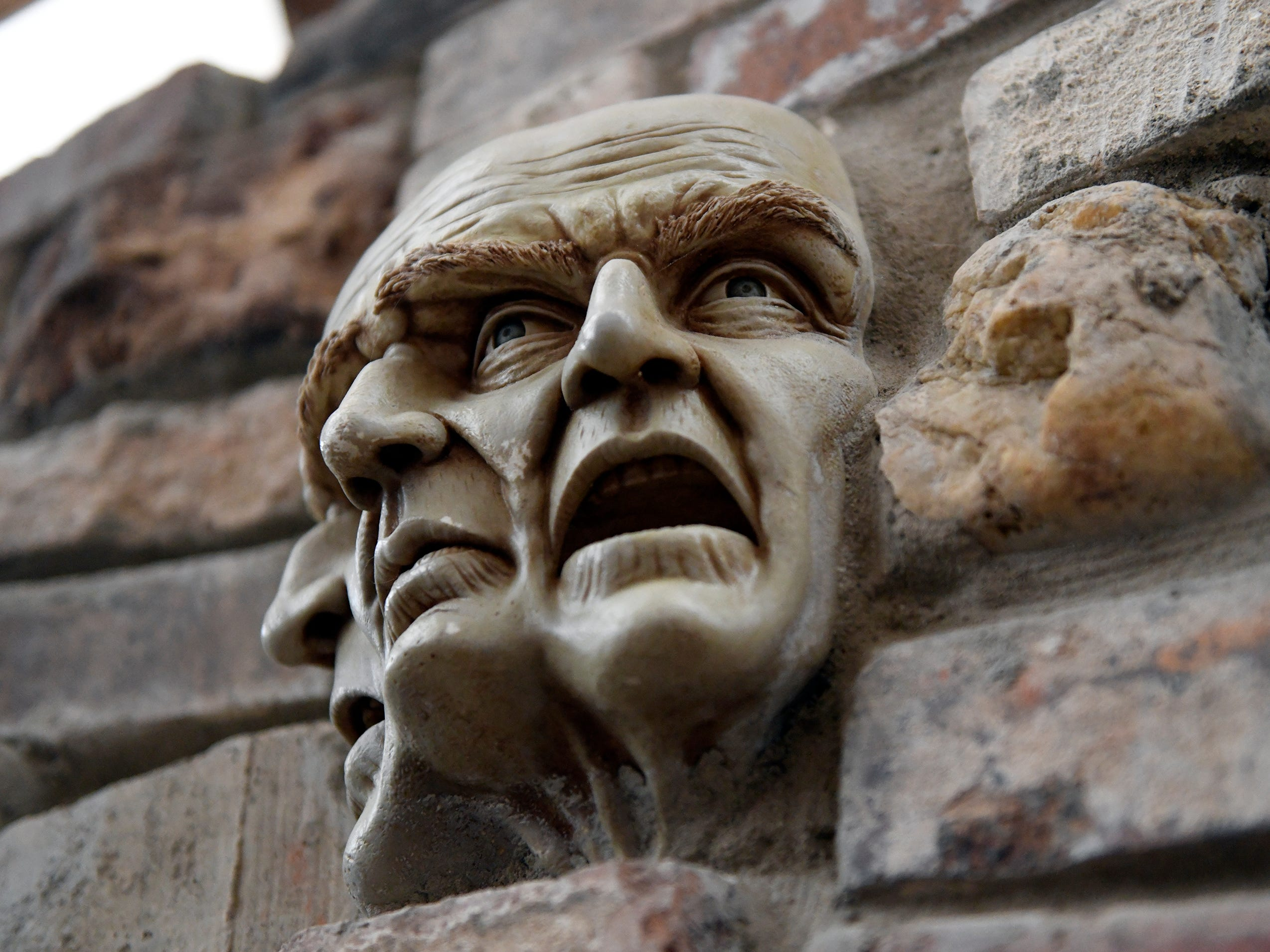 The brick walls at Palace of Depression, on Mill Road in Vineland, are adorned with many small ceramic figures, glass bottles and various metal trinkets including this three faced head.