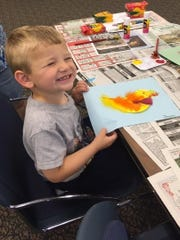 Dean Cramer, 2, of Hopewell shows off a painting he created during a Wee Read program at the Cumberland County Library in Bridgeton.