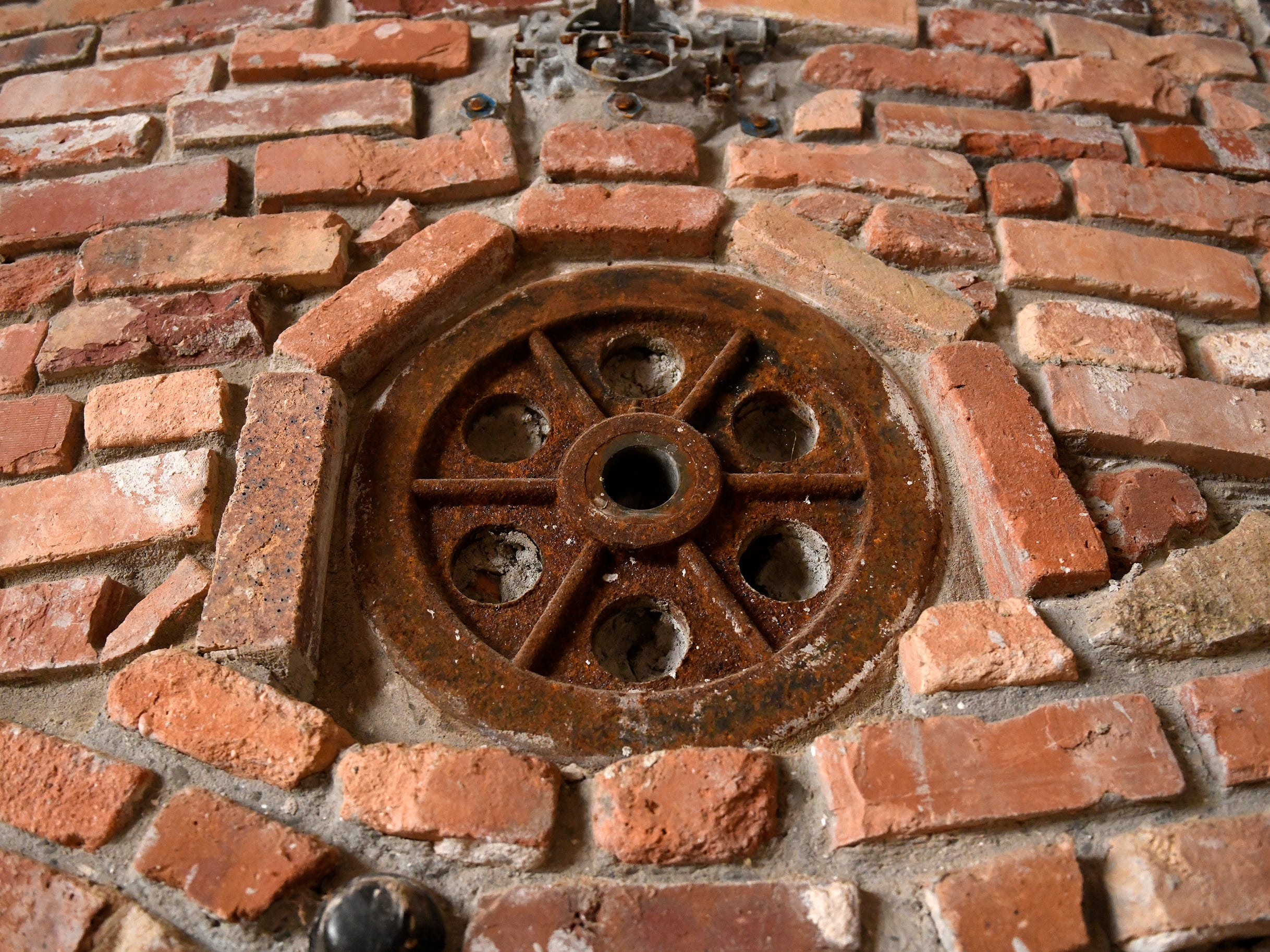 Various metal trinkets, cast concrete figures and colored glass bottles are embedded throughout the brick walls of the Palace of Depression including this metal flywheel.
