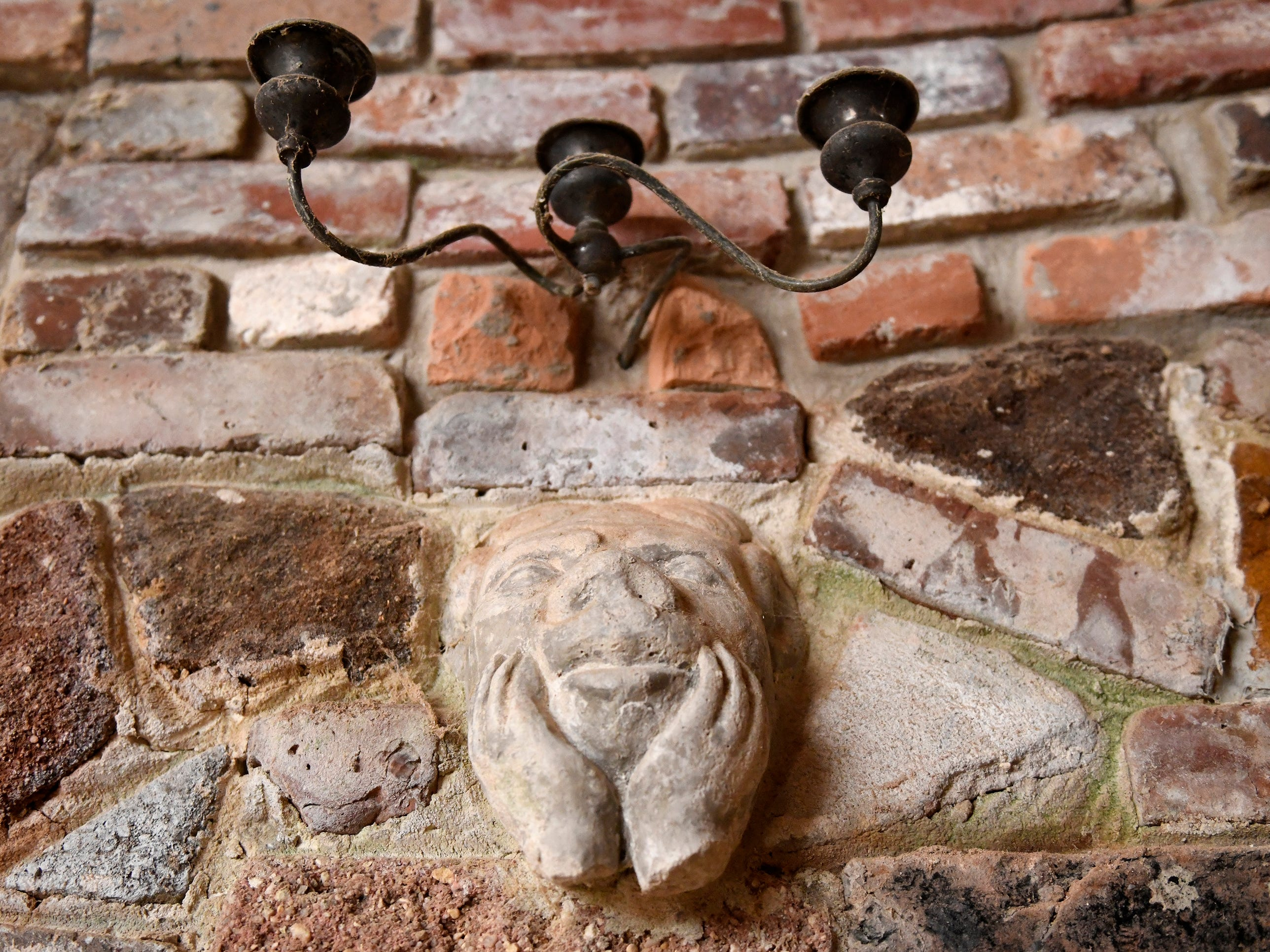 Various metal trinkets, cast concrete figures and colored glass bottles are embedded throughout the brick walls of the Palace of Depression on Mill Road in Vineland.
