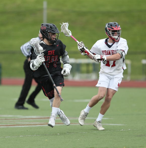 Rye's Johnny Hartzell (44) works against Byram Hills' Jack Kovensky (17) during their 8-3 win in boys lacrosse action at Byram Hills High School in Armonk on Thursday, May 9, 2019.