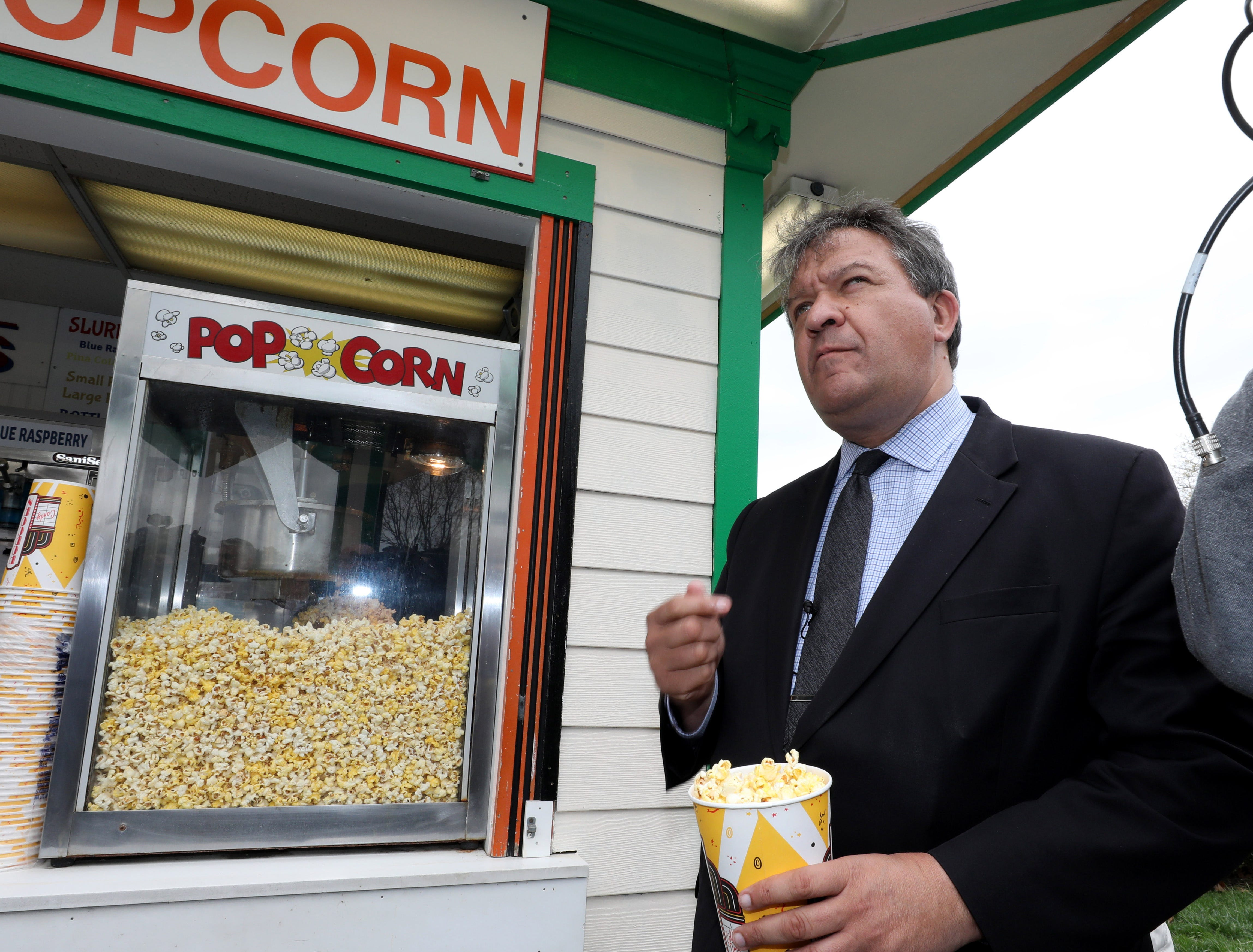 """George Latimer, the Westchester County Executive, samples the popcorn during a """"ride and food safety tour"""" for the media, at Playland in Rye, May 9, 2019."""