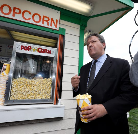 "George Latimer, the Westchester County Executive, samples the popcorn during a ""ride and food safety tour"" for the media, at Playland in Rye, May 9, 2019."