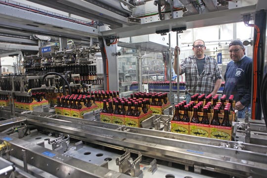 Workers oversee the assembly line as 12-ounce 90-minute IPA's are bottled and packaged in the then-new bottling center at Dogfish Head Brewery in 2014.