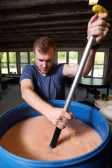 Hocking College fermentation science student Ben Saunders stirs the mash that will become moonshine at Hocking's distillery in New Straitsville.