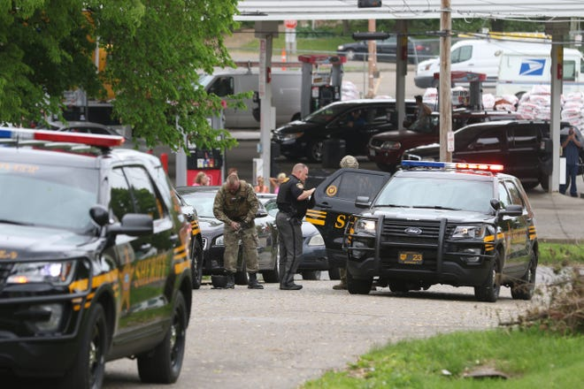 One man is placed in a sheriff office's vehicle at the scene.