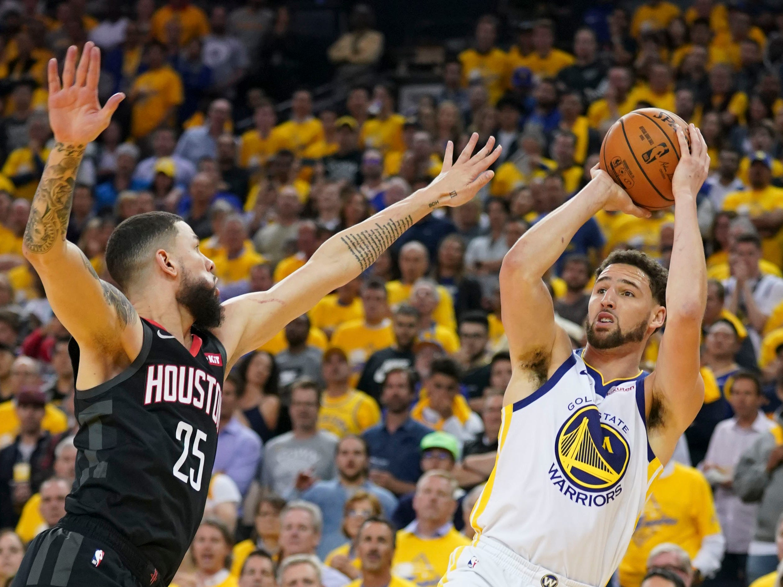 May 8: The Golden State Warriors' Klay Thompson shoots the basketball against Houston Rockets guard Austin Rivers during the fourth quarter of Game 5 at Oracle Arena. The Warriors won the game, 104-99, to take a 3-2 series lead.