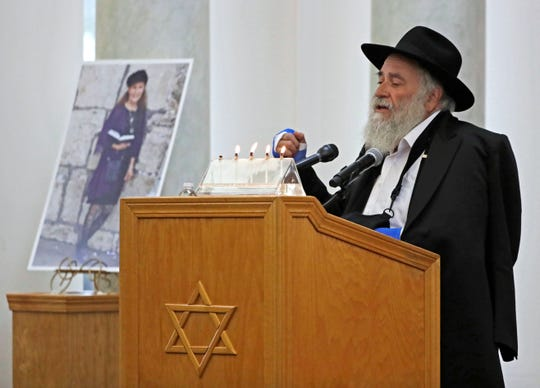 Yisroel Goldstein, Rabbi of Chabad of Poway, speaks Monday, April 29, 2019, during the memorial service for Lori Kaye, who is pictured at left, in Poway, Calif. Kaye was was killed April 27 when a gunman opened fire inside the Chabad of Poway synagogue. Goldstein was injured in the shooting.