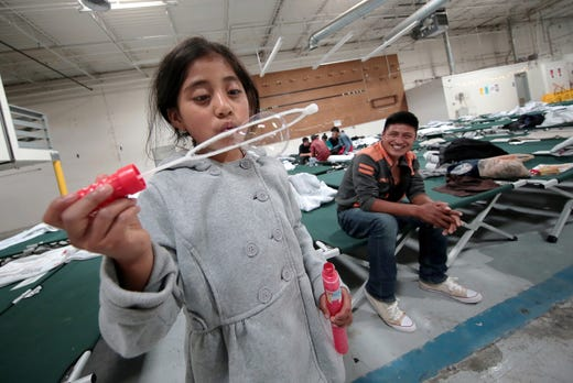 """Guatemalan asylum seeker Miley blows bubbles at the new Casa del Refugiado in east El Paso, Texas, as her father Jaime looks on. Jaime said their life in Guatemala was getting very dangerous. """"There are people who will kill you for a quetzal or your cell phone. People board the bus with a gun and rob everybody."""" he said. """"It's hard to live there."""""""