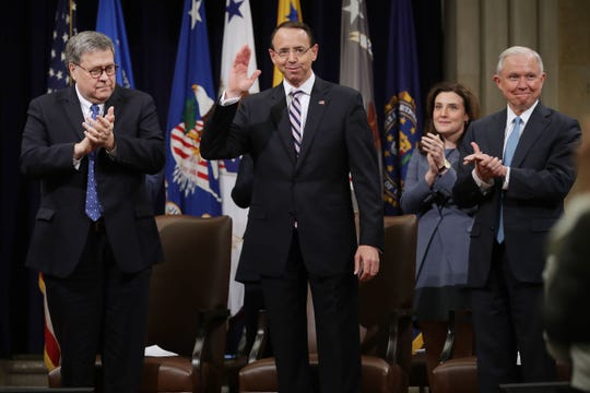Attorney General William Barr and former Attorney General Jeff Sessions, right, applaud Deputy Attorney General Rod Rosenstein during his farewell ceremony at the Justice Department on May 9, 2019.