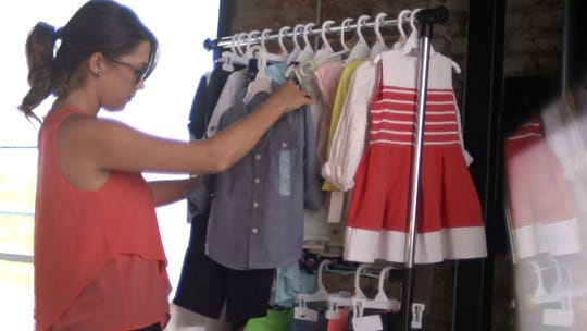 A stylist at Wee Blessing of Columbus, Georgia, hand-selects children's clothes for a client.