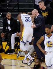 Golden State Warriors forward Kevin Durant walks off the court with an injury against the Houston Rockets.