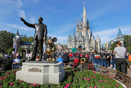 Guests watch a show near a statue of Walt Disney and Micky Mouse in front of the Cinderella Castle at the Magic Kingdom at Walt Disney World in Lake Buena Vista, Fla. in January 2019.