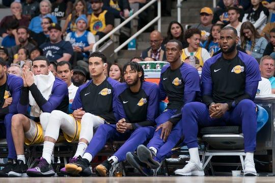 Lakers guard Lonzo Ball (left), forward Kyle Kuzma, forward Brandon Ingram, guard Rajon Rondo, and forward LeBron James watch from the bench during a game.