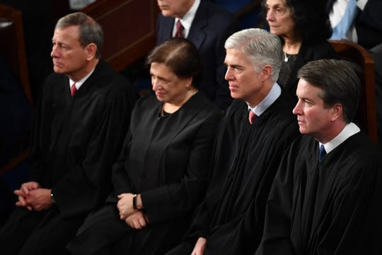 New Supreme Court Associate Justice Brett Kavanaugh, right, listens to President Trump's State of the Union address in February along with Chief Justice John Roberts, left, and Associate Justices Elena Kagan and Neil Gorsuch.