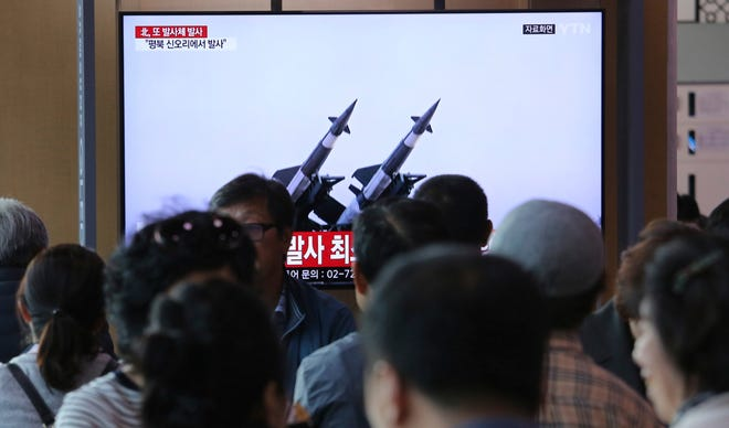 People watch a TV at a train station in Seoul, South Korea, showing file footage of North Korea's missiles on May 9, 2019.