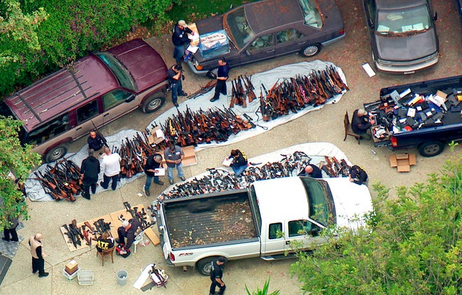 This photo from video provided by KCBS/KCAL-TV shows investigators from the U.S. Bureau of Alcohol, Tobacco, Firearms and Explosives and the police inspecting a large cache of weapons seized at a home in the affluent Holmby Hills area of Los Angeles on May 8, 2019.