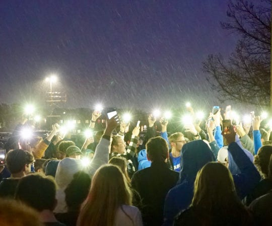 Standing in the pouring rain with their phone flashlights illuminated, students from the STEM School in Highlands Ranch, Colorado, hold a vigil outside a gun-control rally on Wednesday evening.