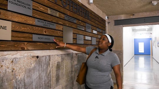 C'alra Bradley points out the name of her former mentor, Nory Angel, on a wall at SER Jobs Houston.