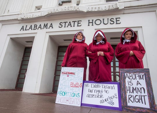 Women dressed as handmaids protest against a near-total abortion ban outside the Alabama State House in Montgomery, Ala., on April 17, 2019.