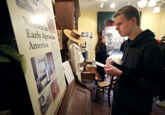 "Josh Peters, a junior at Neenah High School, reads through an informational board at the Neenah Historical Society's new exhibit ""Voting for a Change: Impact of the 19th Amendment on our Community."""