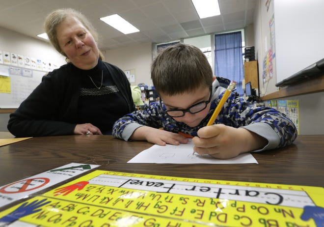 Paraprofessional Diane Conrad helps Carter Feavel write out the alphabet during his intellectual disabilities cross categorical special education class at Huntley Elementary School in Appleton.