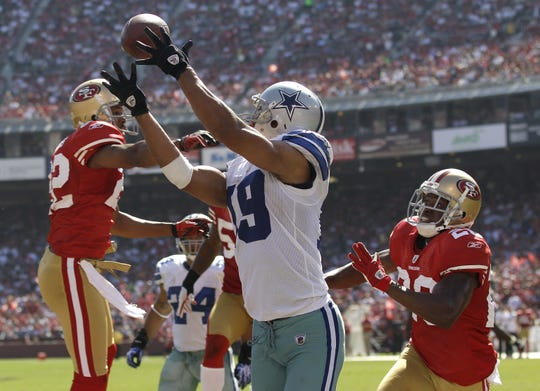 Dallas Cowboys wide receiver Miles Austin (19) catches a five-yard touchdown pass from quarterback Jon Kitna in between San Francisco 49ers cornerback Carlos Rogers (22) and safety Madieu Williams (20) in the third quarter of an NFL football game in San Francisco, Sunday, Sept. 18, 2011.  (AP Photo/Marcio Jose Sanchez)