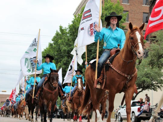 Cowgirls wave from horses at the start of Thursday evening's Western Heritage Classic parade in downtown Abilene. The annual May event continues Saturday at the Taylor County Expo Center.