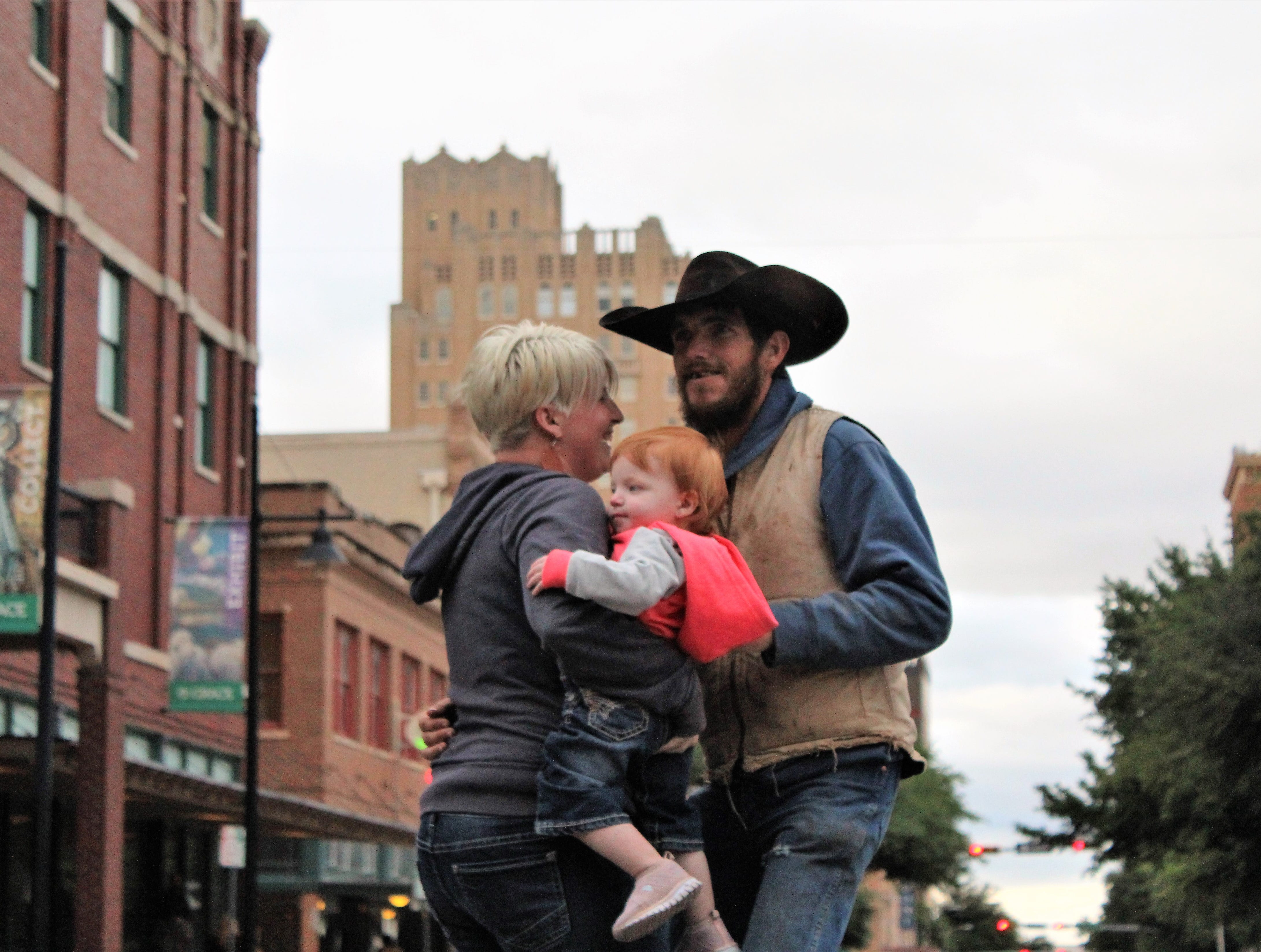 Chancey and Cara Lee scoot their boots while cradling Laramie, 15 months, at the street dance on the star in downtown Abilene on a brisk and gray Thursday evening. May 9, 2019