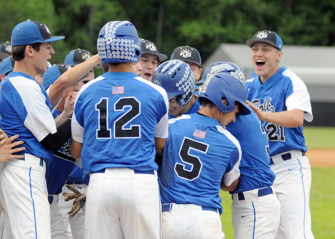 Polk County players swarm Nick Capozzi after his grand slam during Thursday's state 1A playoff game. Capozzi had two homers in the Wolverines' 7-6 win.