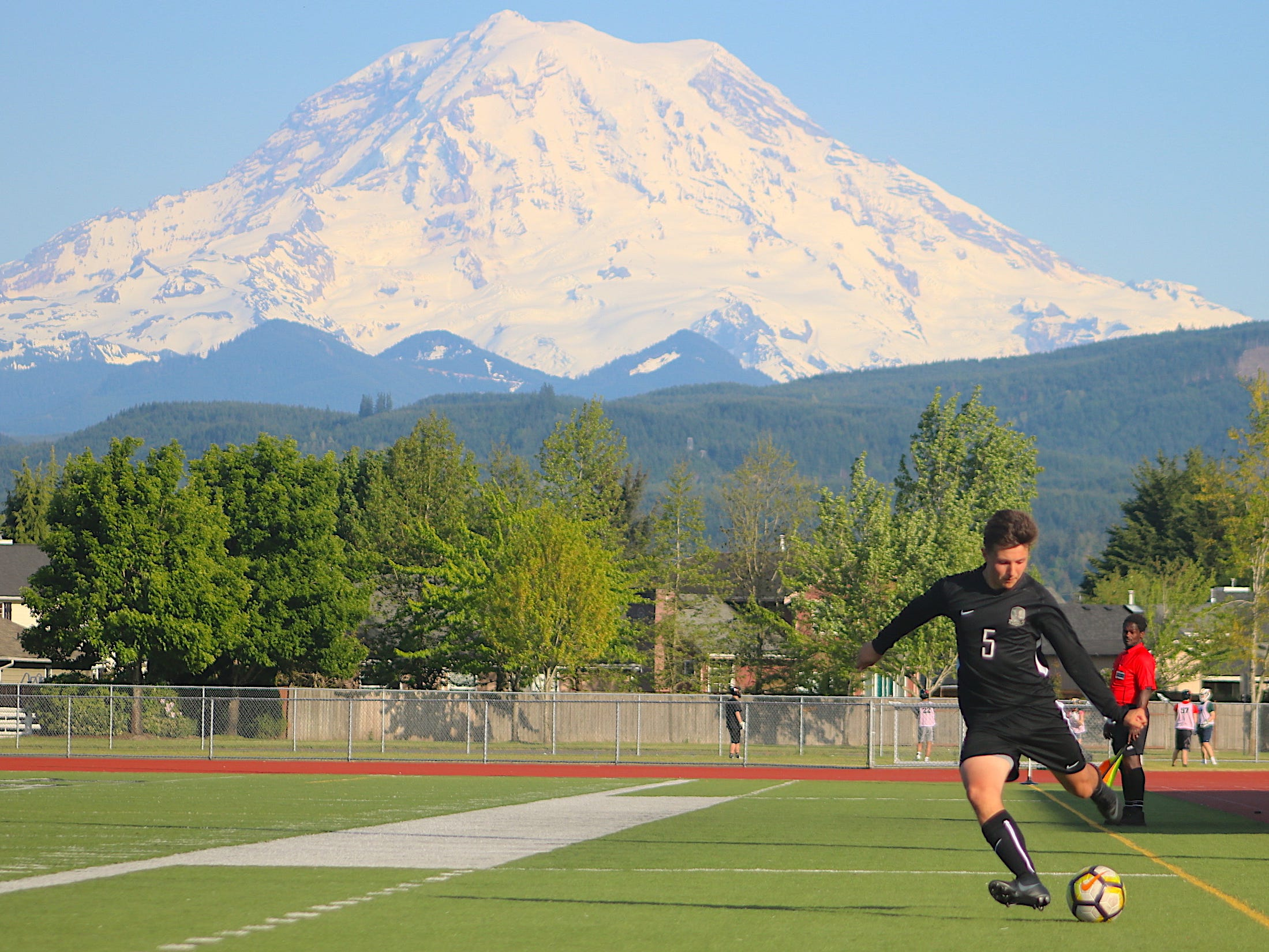 Klahowya's Logan Brunson takes a free kick as Mount Rainier looms in the background during Thursday's playoff game against Vashon Island at Orting High School.