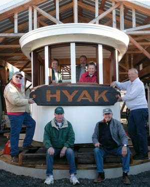 Poulsbo Historical Society members stand with the replica Hyak pilothouse at the Poulsbo Maritime Museum.