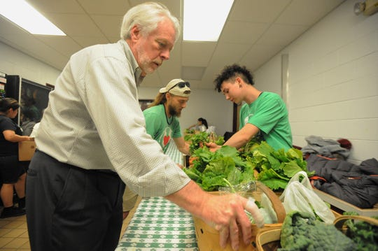 Bounty & Soul executive director Bruce Ganger works alongside staff and volunteers to prepare for a market at Owen Middle School on May 9. The Black Mountain-based nonprofit is one of 17 organizations to receive grants totaling more than $100,000 this year.