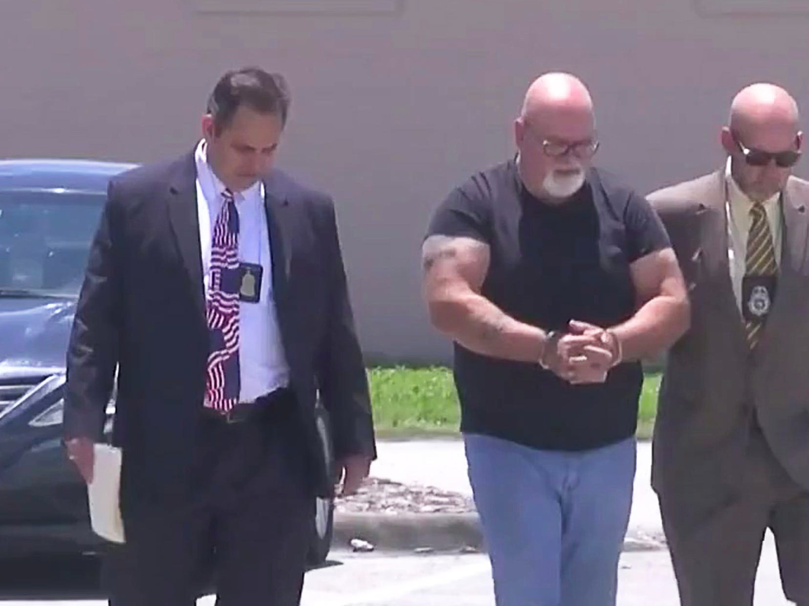 Former Palm Bay Deputy city manager Dave Isnardi being led into the Brevard County Detention Center Friday afternoon.  Photo courtesy WKMG News 6.