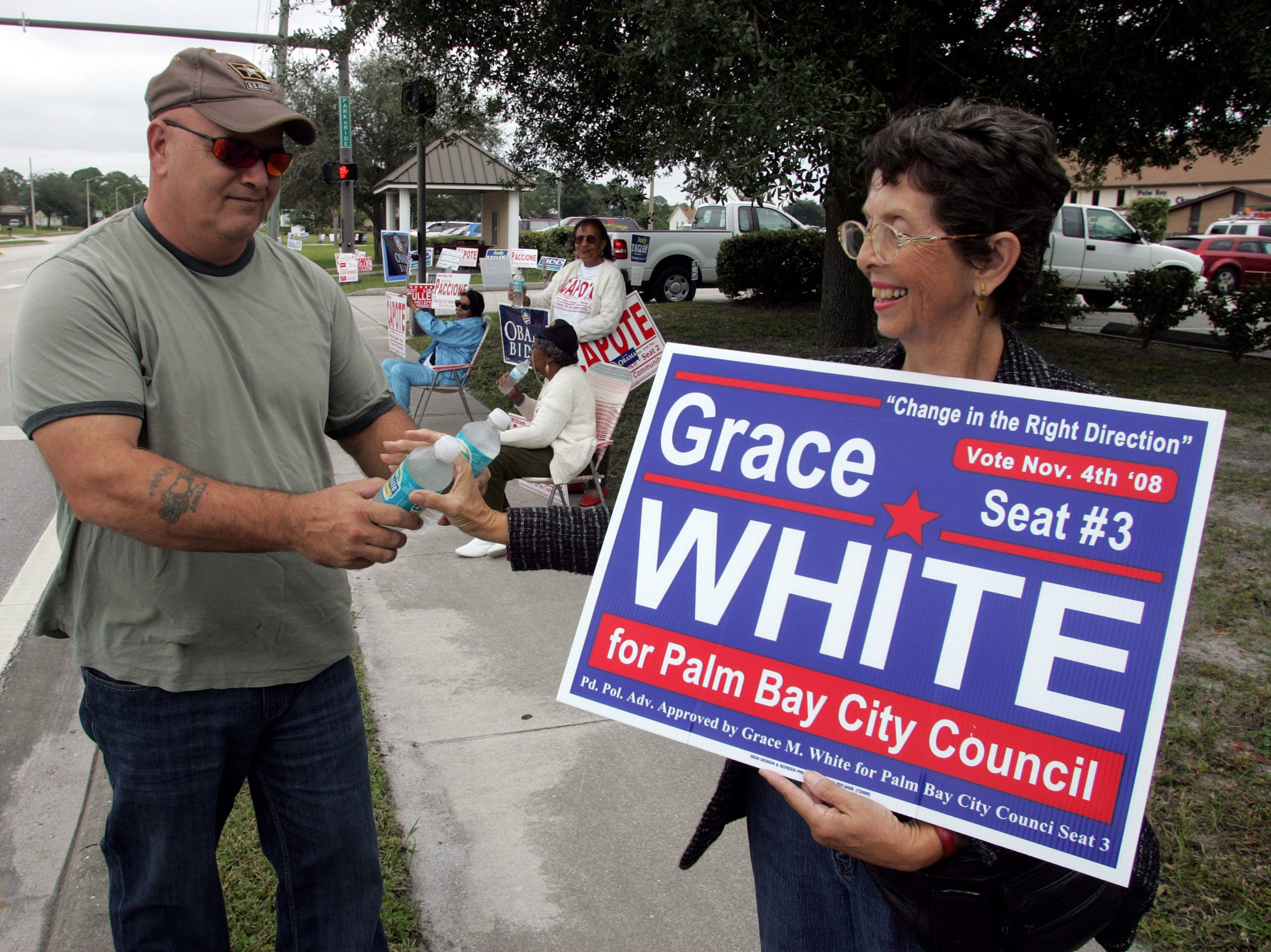 David Isnardi, left, husband of then-City Council member Kristine Isnardi, gives free water to volunteer Mary Mann while she waved campaign signs to passers-by and voters entering precincts 110 and 219 at Palm Bay Christian Church during voting day in Palm Bay on Nov. 4, 2008.