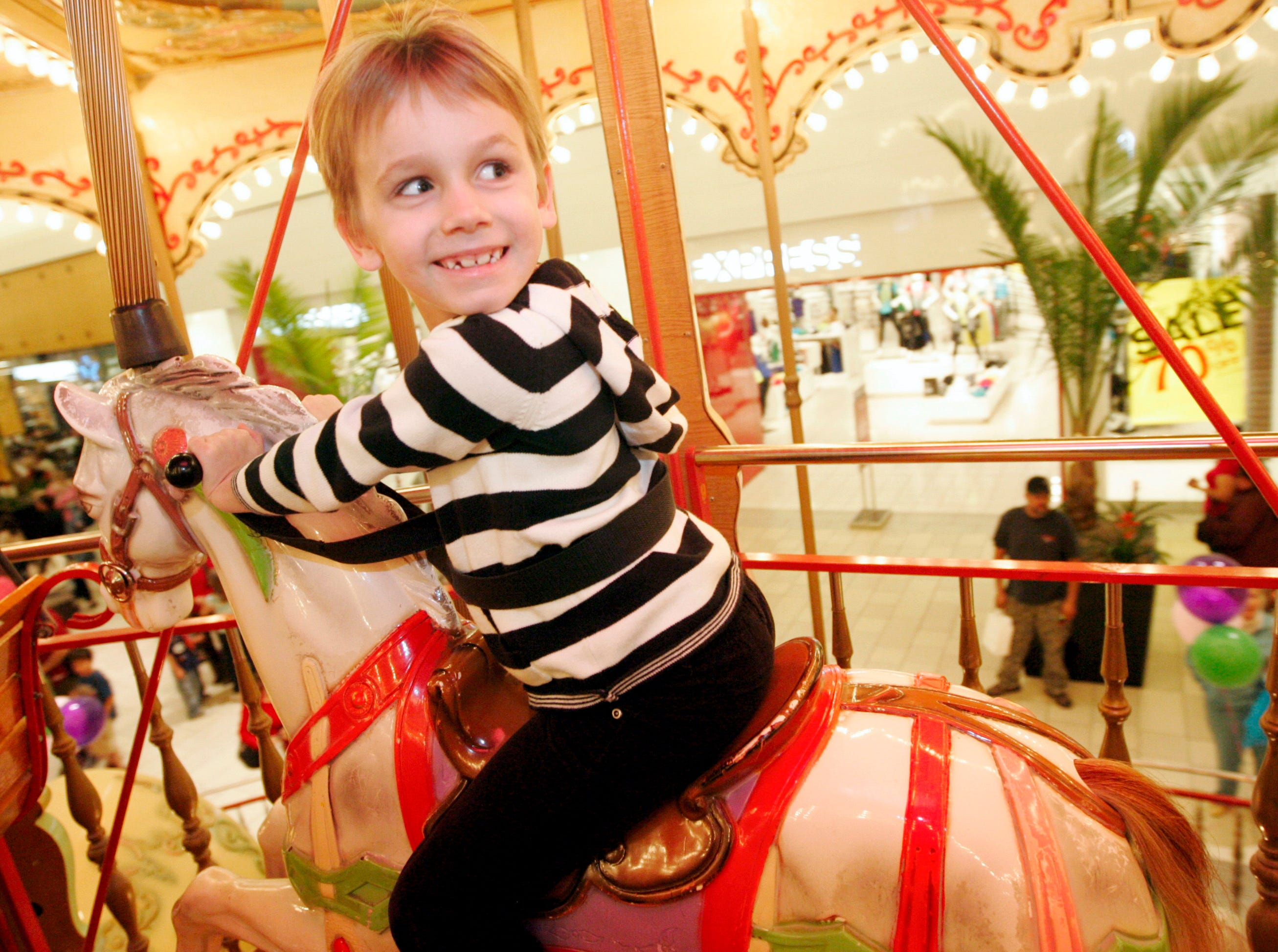 Angelica Fritz, 6 of Corpus Christi, looks back at her grandmother as she and her siblings take a ride on upper deck of the carousel Saturday, Jan. 31, 2009 at La Palmera mall in Corpus Christi.