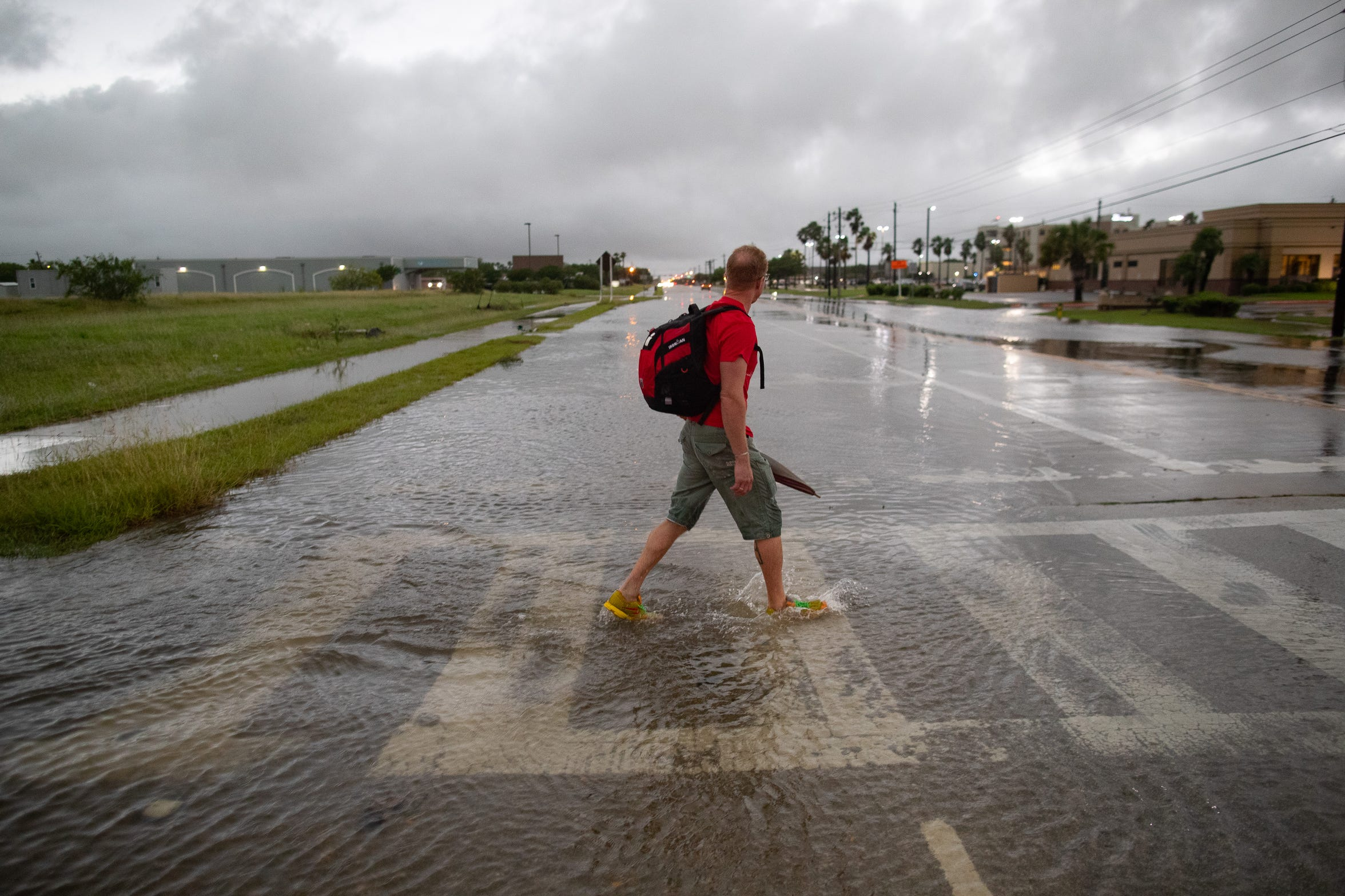 A man walks through water as he crosses Williams Drive at  Rodd Field Road after heavy rains fell in the early morning on Friday, May 10, 2019.