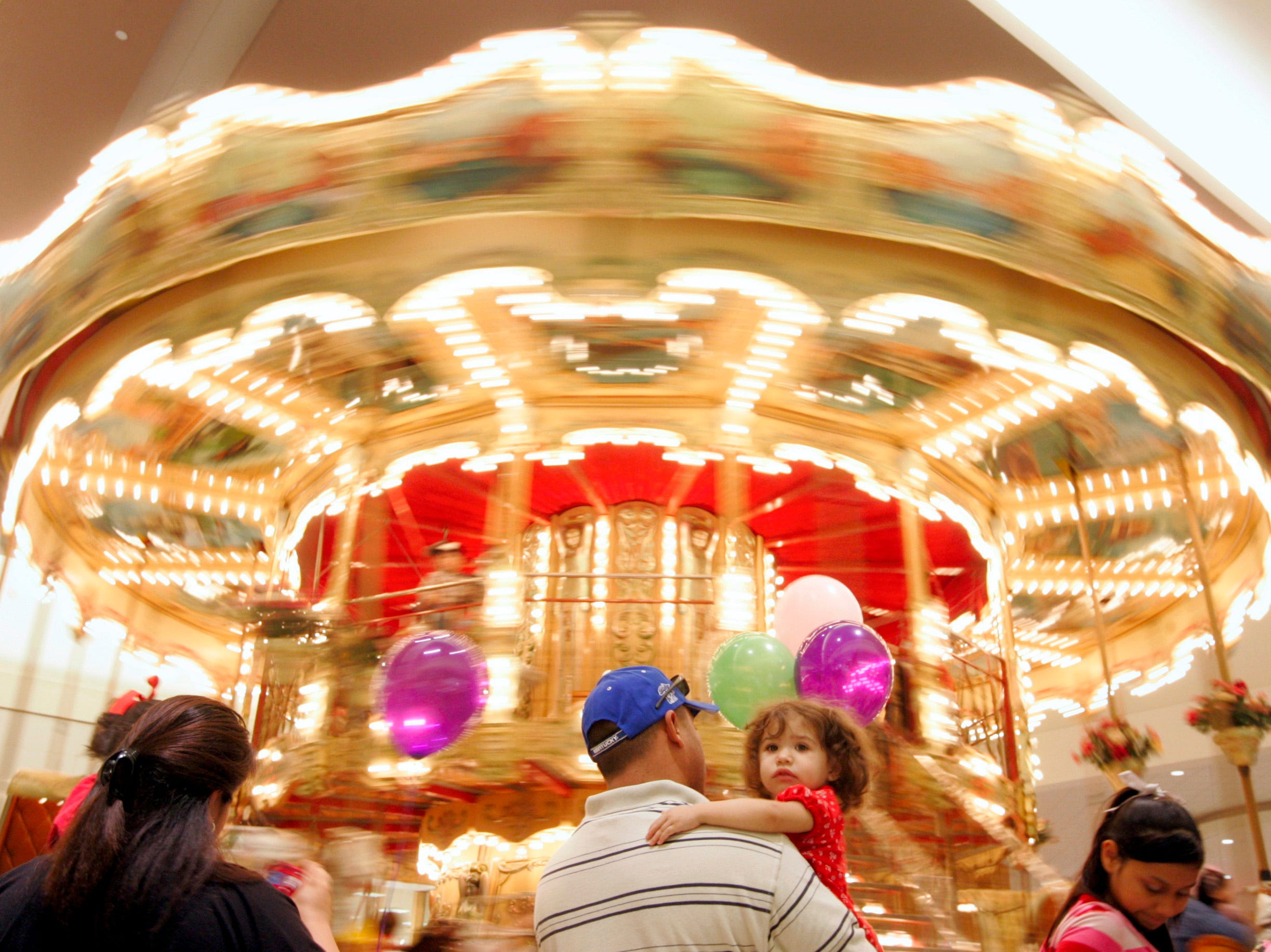 2-year-old Alexis Atkinson waits in line with her father, Ector, before taking a spin on the carousel Saturday, Jan. 31, 2009 at La Palmera mall in Corpus Christi. A steady flow of customers came out for a final ride before the carousel was dismantled and removed from the mall.