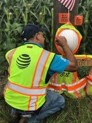 An AT&T employee signs a hard hat on a cross near the site of a fatal crash on State Highway 359.