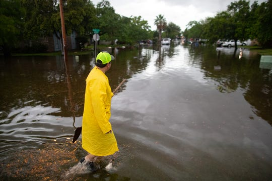 George Cabrera clears garbage from flood waters on Ursa Drive after heavy rains fell in the early morning on Friday, May 10, 2019.