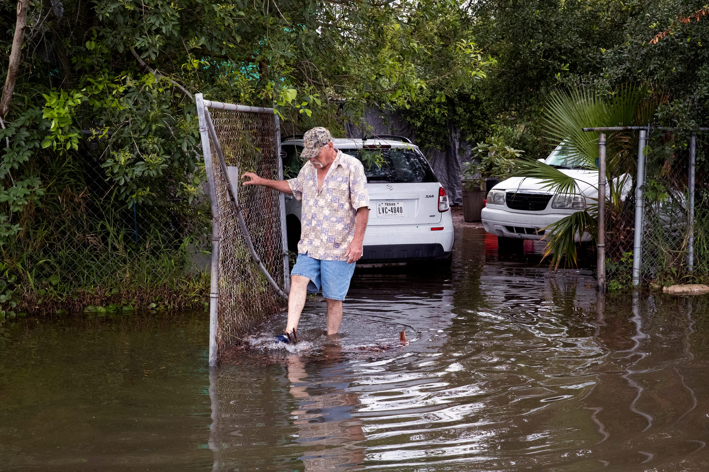 Joe Gonzalez walks through flood waters outside his home on Flour Bluff Drive following heavy rains on Friday, May 10, 2019.
