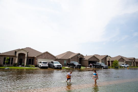 Two kids play in middle of a flooded Ellie Drive after heavy rains over night flooded the area on Friday, May 10, 2019.