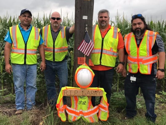 AT&T employees stand by a cross near the site of a fatal crash on State Highway 359. They assembled a wooden cross with safety gear to honor another employee who was killed in a car crash May 2, 2019.